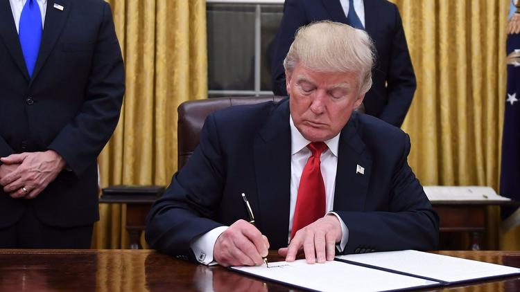 President Donald Trump signing his executive order undermining the Affordable Care Act on Jan. 20. (Jim Watson / AFP/Getty Images)